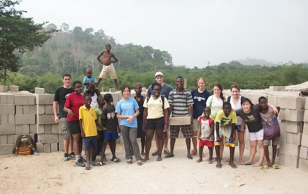 Students stand with local children on a service site in Ghana