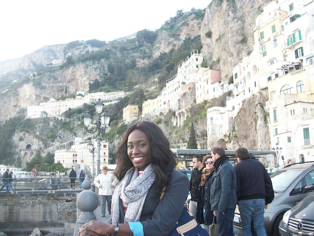A woman smiles in front of the famous cliffside architecture on the Amalfi Coast in Italy