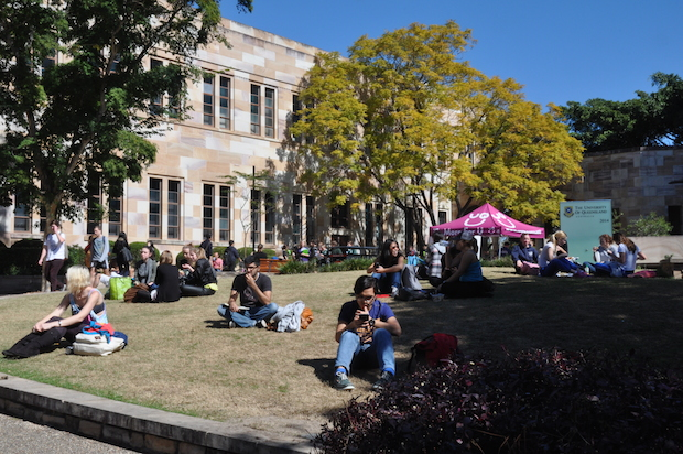 Students sit on a sunny quad on University of Queensland's campus