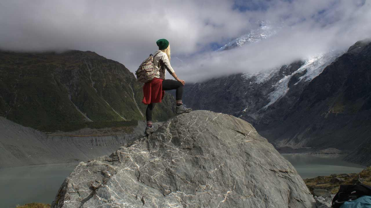 A girl poses on a rock facing cloud covered mountains in New Zealand
