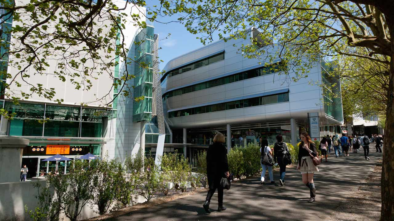 Students walk along a courtyard between two buildings on University of Auckland's campus