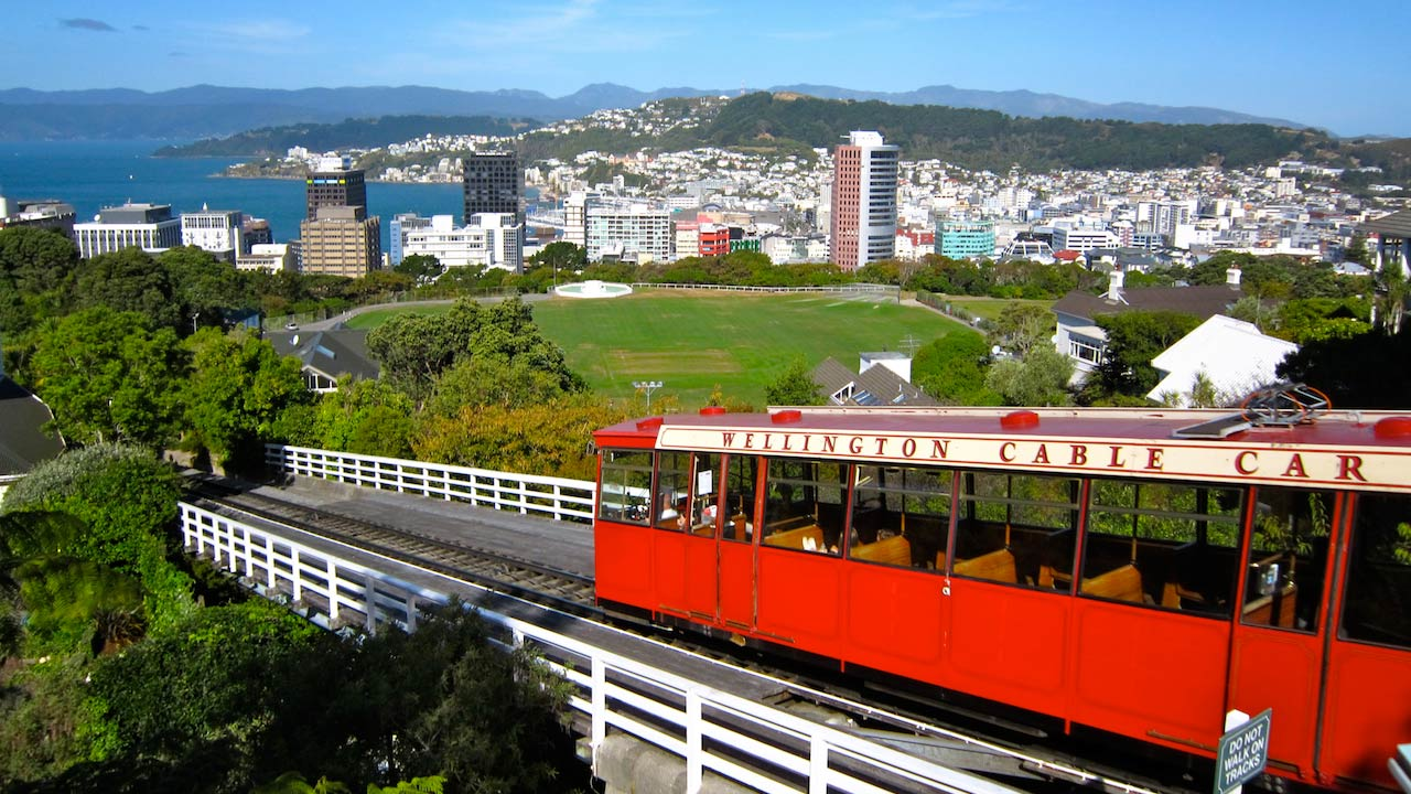 A red cable car traveling past a beautiful view of the city of Wellington