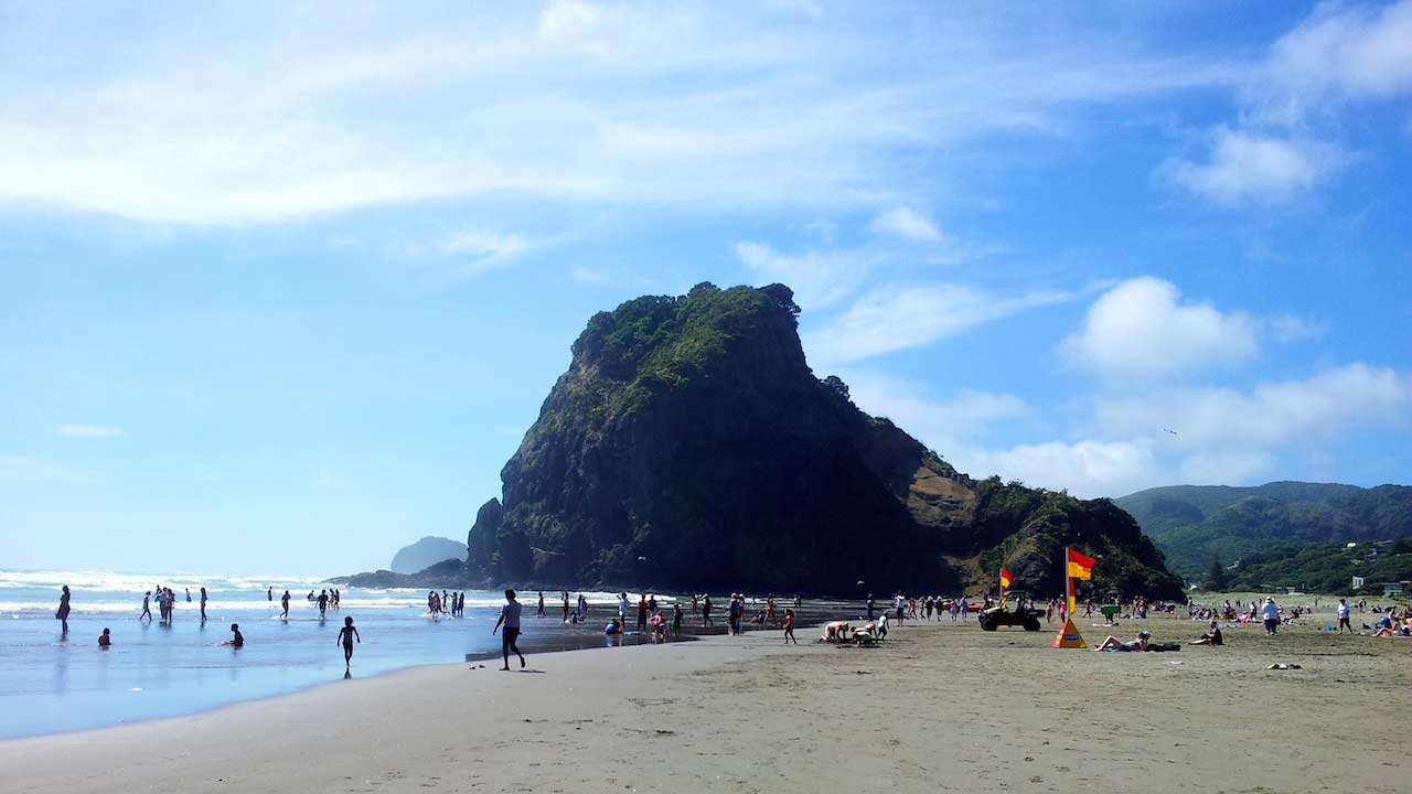 Sandy shores and cliff rock face at a beach in Auckland, New Zealand
