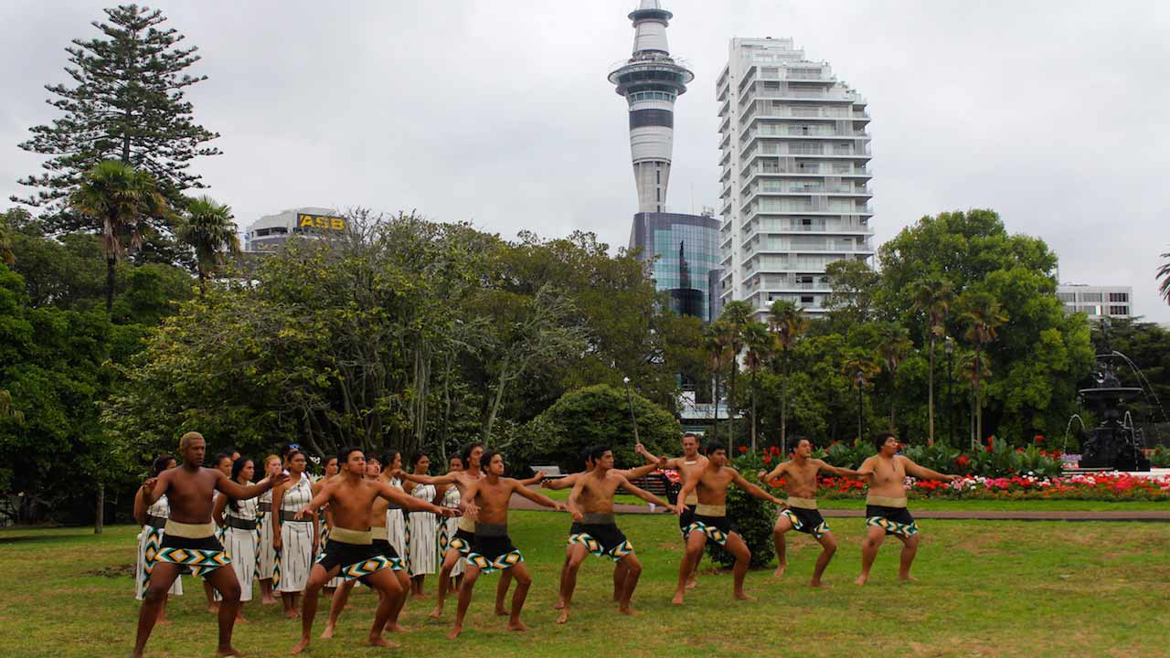 Maori men dressed in traditional attire perform a ceremony in a park in Auckland, New Zealand