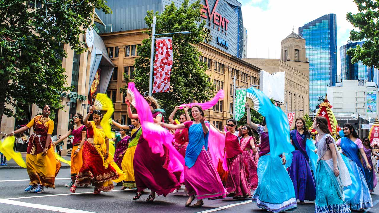 Colorfully dressed women dance in the street during a parade in Auckland, New Zealand