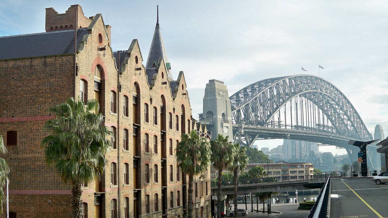 The sun hitting a row of brick buildings and the Sydney Harbor Bridge in the background