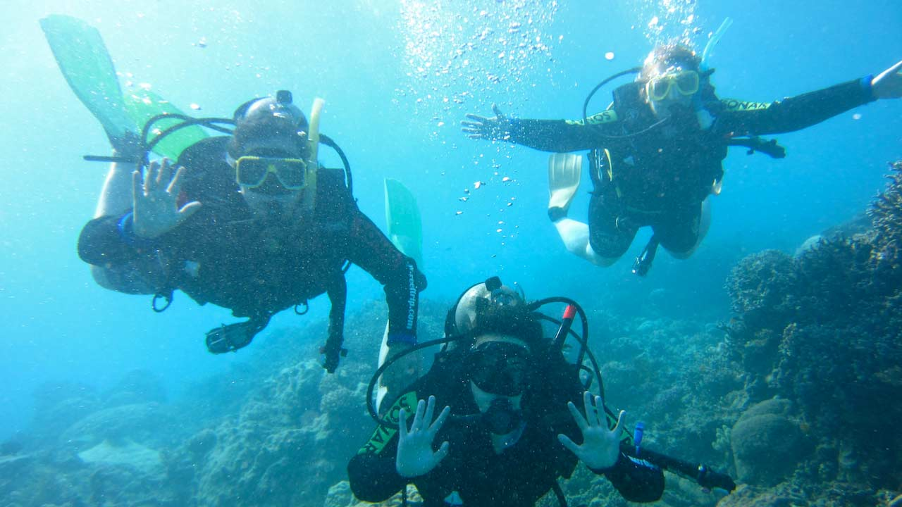 Three students posing underwater while scuba diving in the Great Barrier Reef