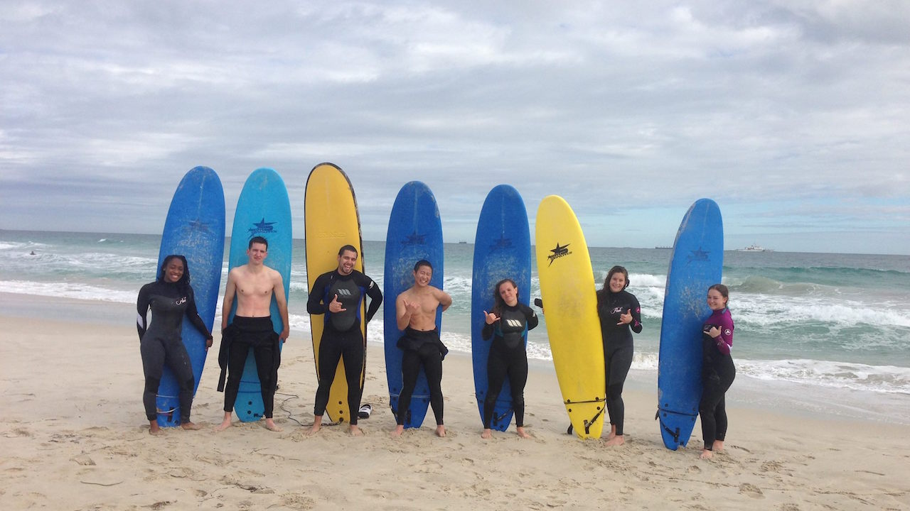 Seven students pose with their surf boards on the beach under a cloudy sky