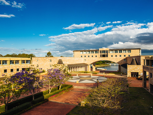 The central area of Bond's campus surrounded by buildings on a sunny day