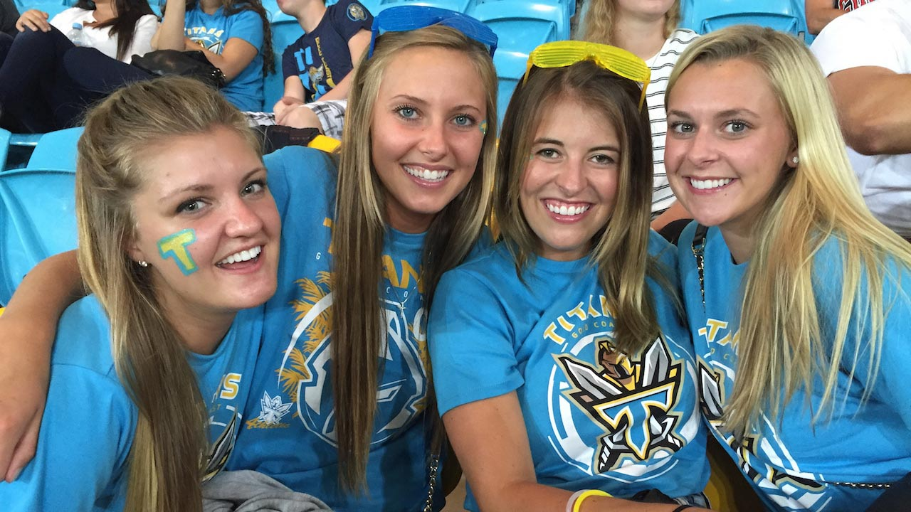 Four women smiling and dressed in school spirit attire