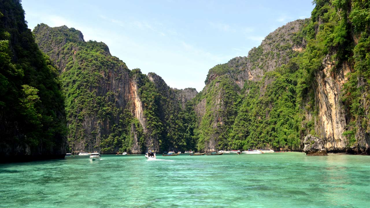 Crystal clear ocean surrounded by limestone cliffs near Railay Beach in Thailand