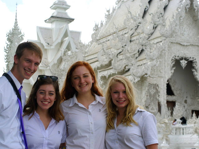 Four students pose outside the White Temple in Chiang Rai, Thailand