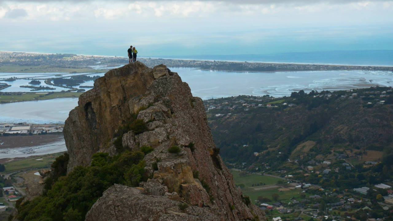 Two people stand on a mountainous peak overlooking a valley in Christchurch, New Zealand