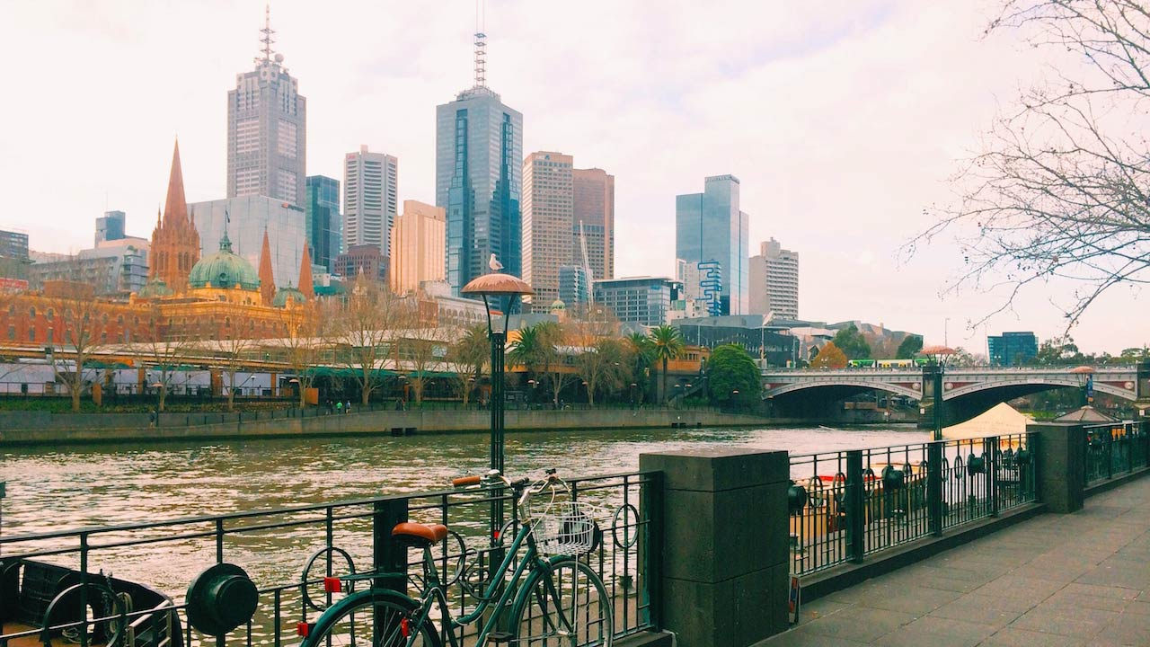 A bicycle leans against an iron fence in front of a river in Melbourne with the city's skyline as a backdrop