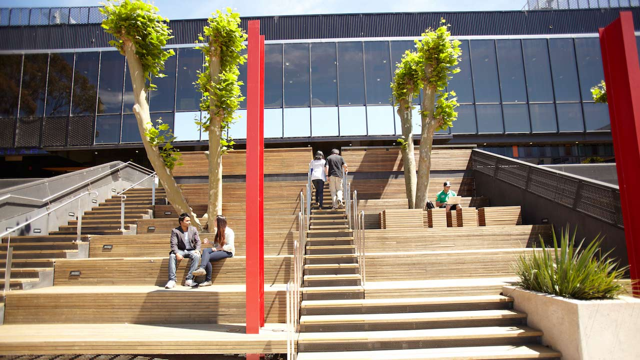A few people sit on large steps outside of a building on Deakin's campus