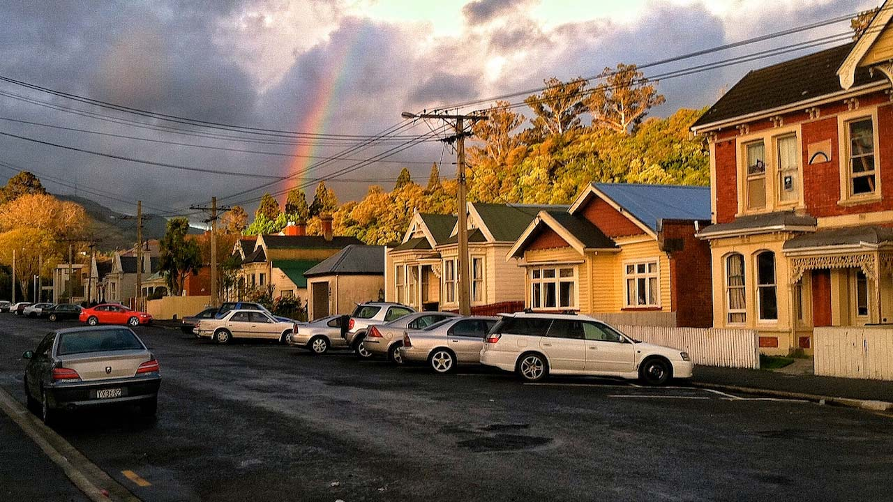 A rainbow peeks out of the cloudy sky behind a row of homes and parked cars in Dunedin, New Zealand