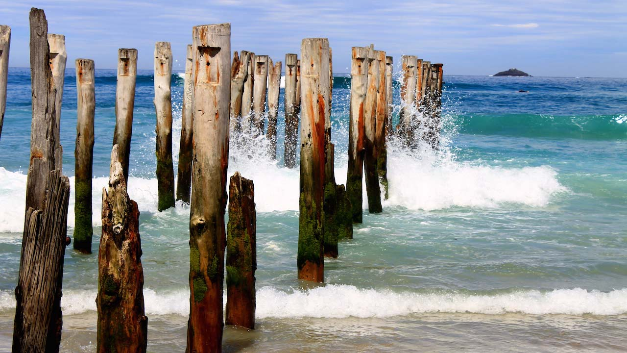 Waves crash into the remaining posts of a wooden boardwalk in Dunedin, New Zealand