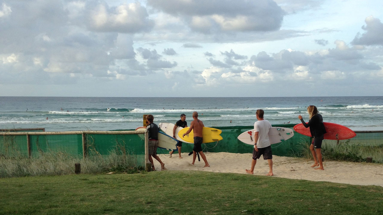 Four people walking with surfboards on a sandy path to the beach on the Gold Coast