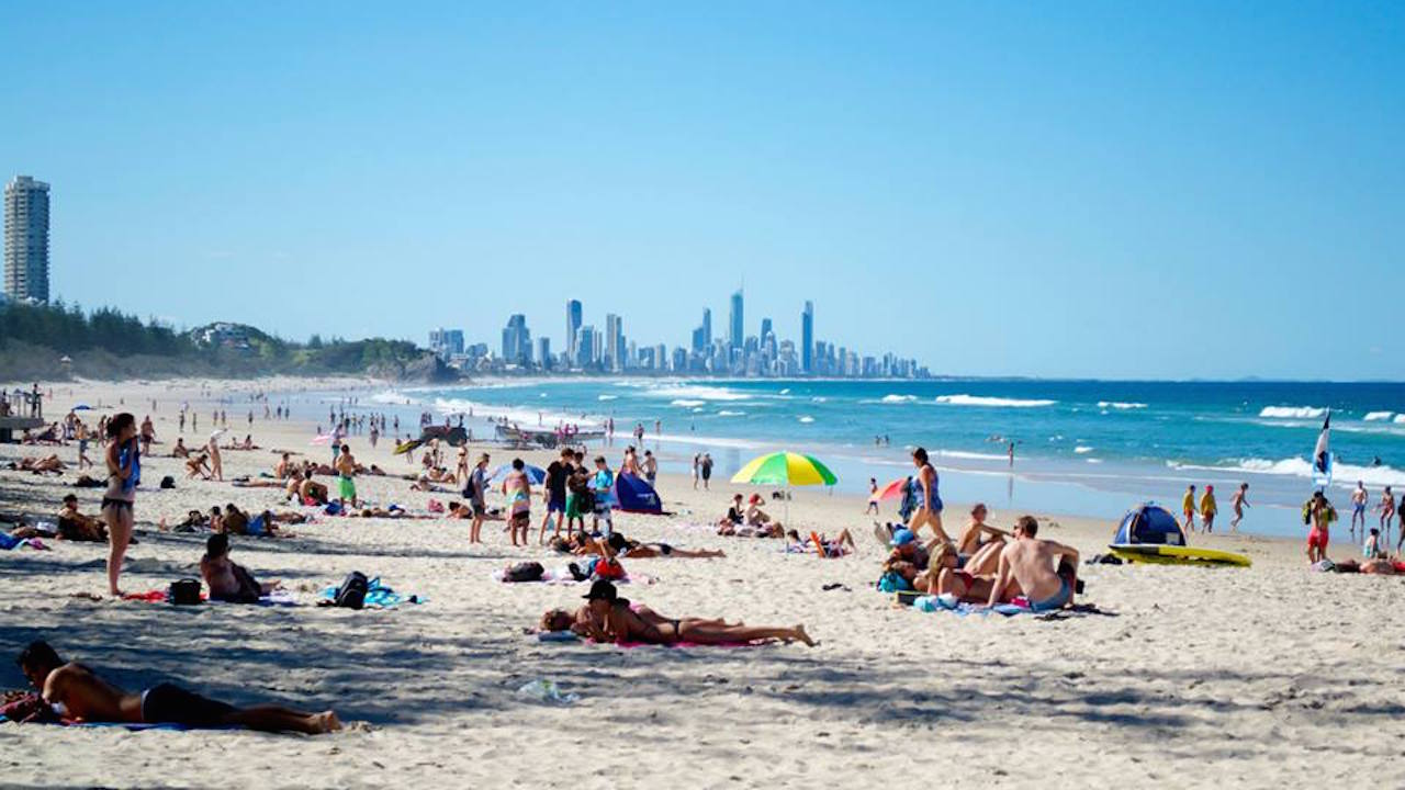 Crowds of people enjoying the Gold Coast's beautiful beach on a sunny day