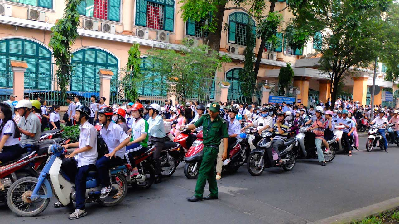 A police officer directs traffic as a hoard of motorbikes drive by on a street in Ho Chi Minh City