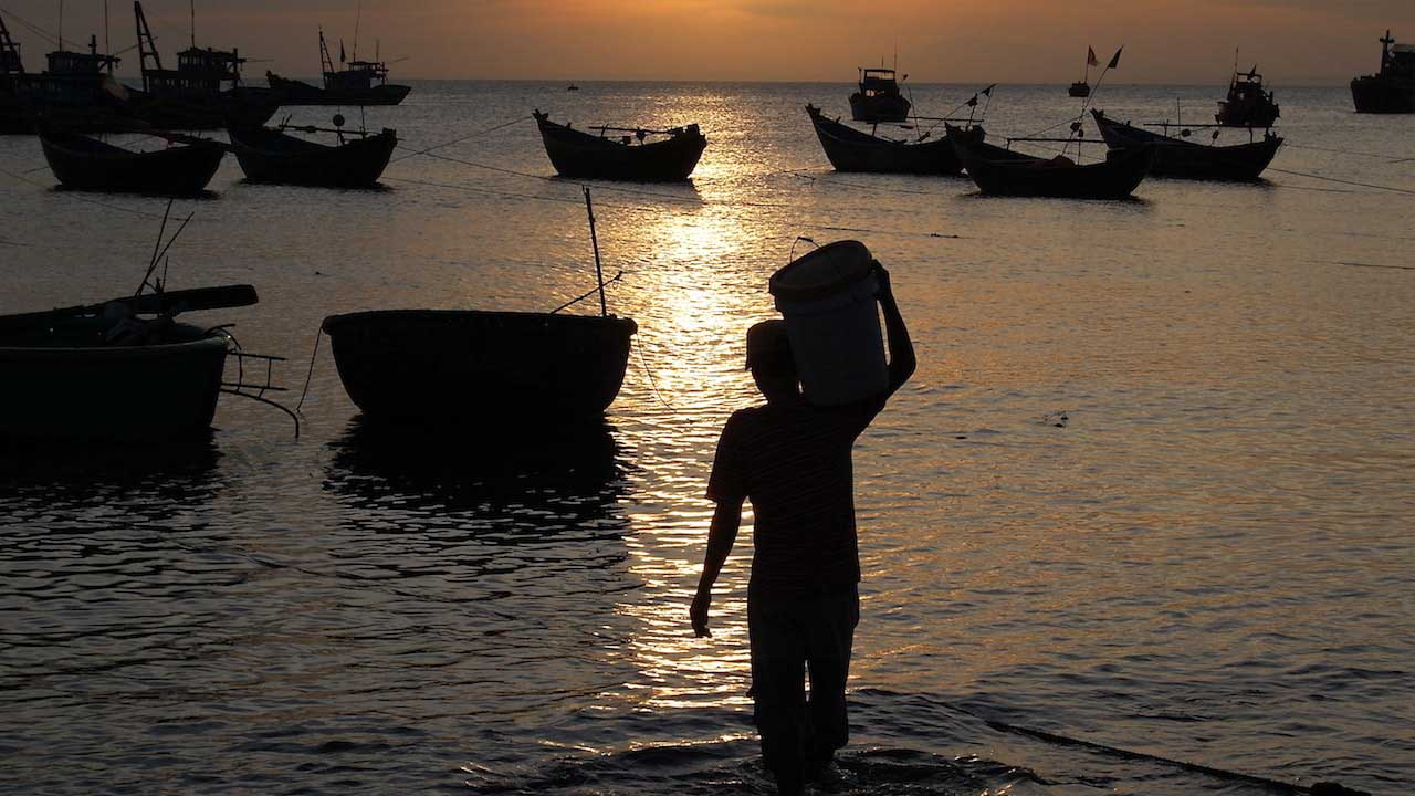 Silhouette of a man holding a bucket walking into the ocean dotted with docked boats at dawn in Vietnam