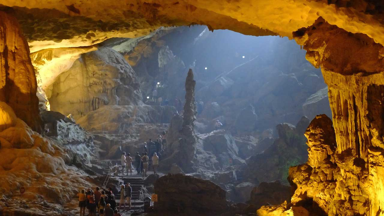 The inside of a large illuminated cave with people exploring in Vietnam