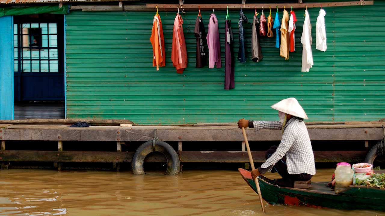 A person rows a canoe passed a teal panel house with colourful laundry hung outside in Vietnam