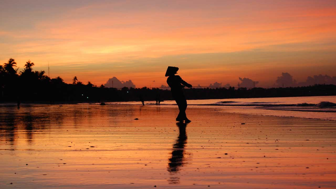 The silhouette of a fisherman casting his line into the shore at dawn in Vietnam