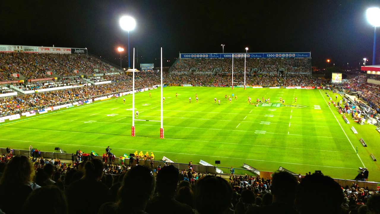 An illuminated football stadium packed with fans during a nighttime match