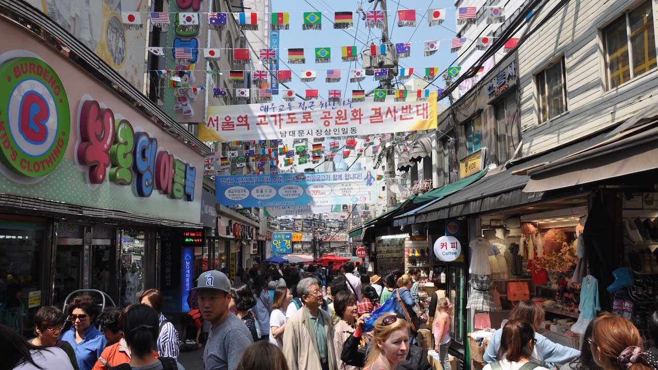 A crowded, laneway in Seoul with multinational flags strewn between buildings