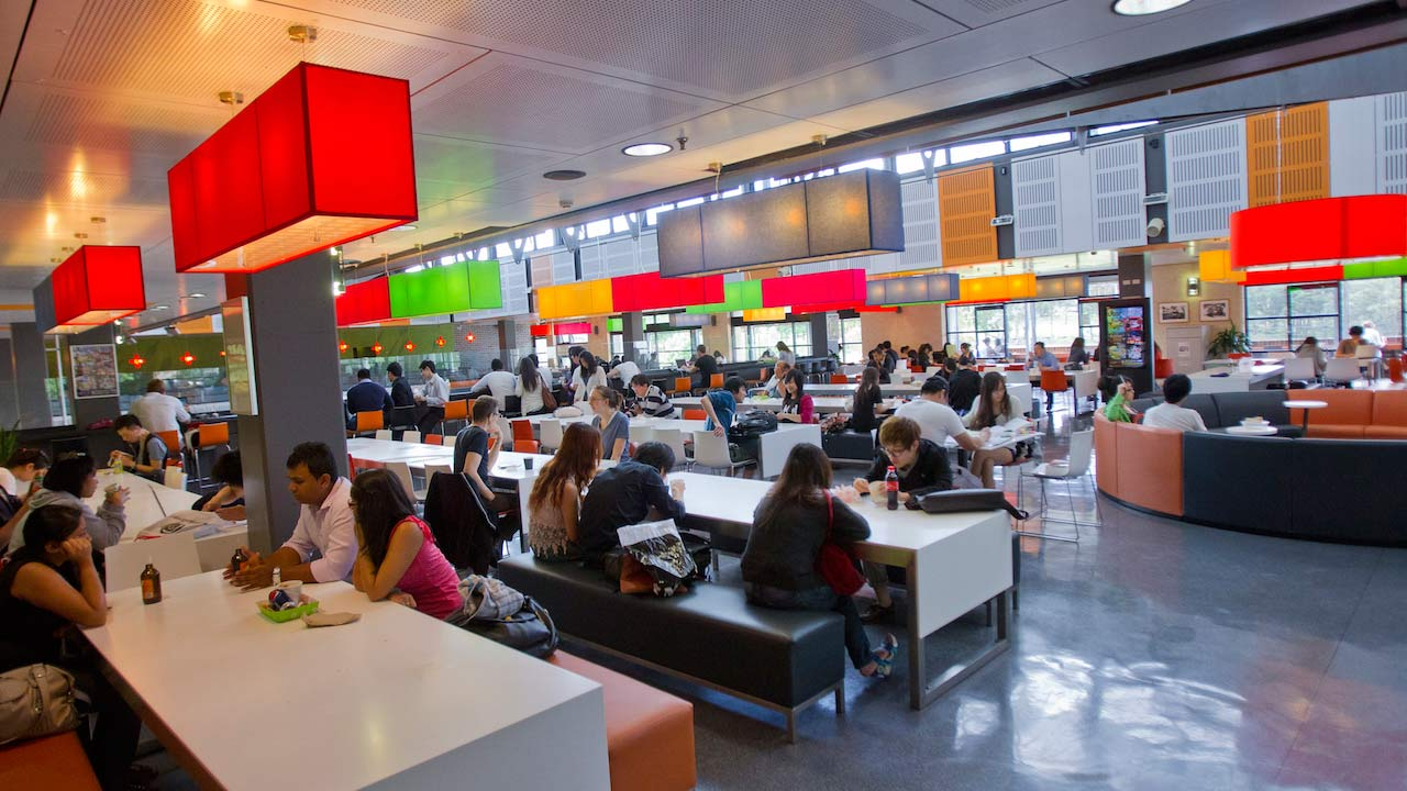 A crowded dining hall is filled with students conversing and eating at Macquarie University near Sydney, Australia