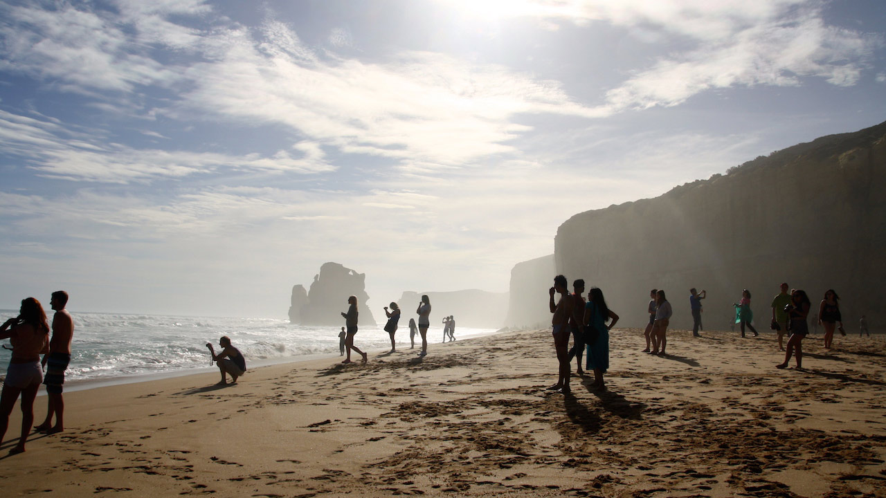 Many people stand along the beach enjoying the beautiful view of the 12 Apostles on a sunny day