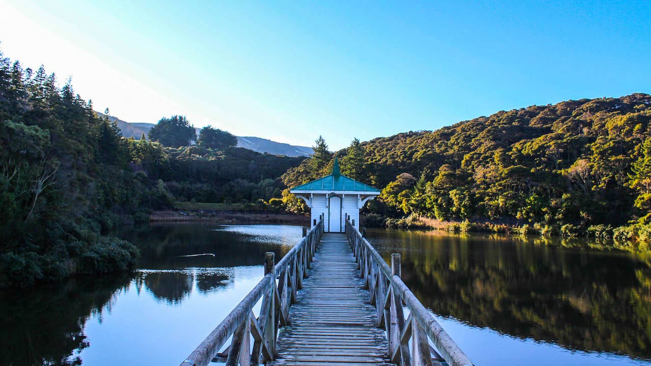 A wooden bridge leading to a house on a crystal clear lake surrounded by mountains near Dunedin, New Zealand