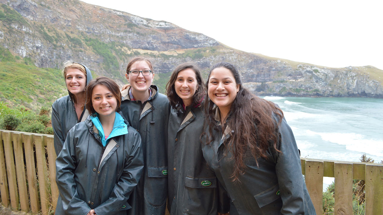 Five women pose smiling in front of a mountain near an ocean