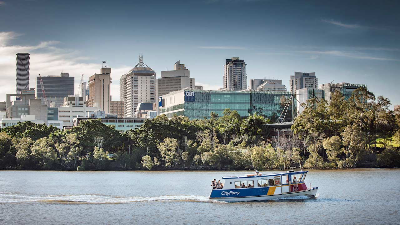 A ferry chugs along the Brisbane River past QUT's campus