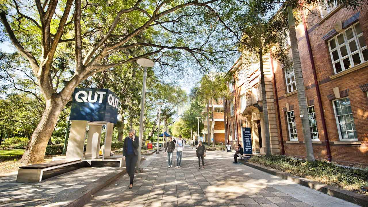 People walk around QUT's Garden Point Campus on a sunny winter day