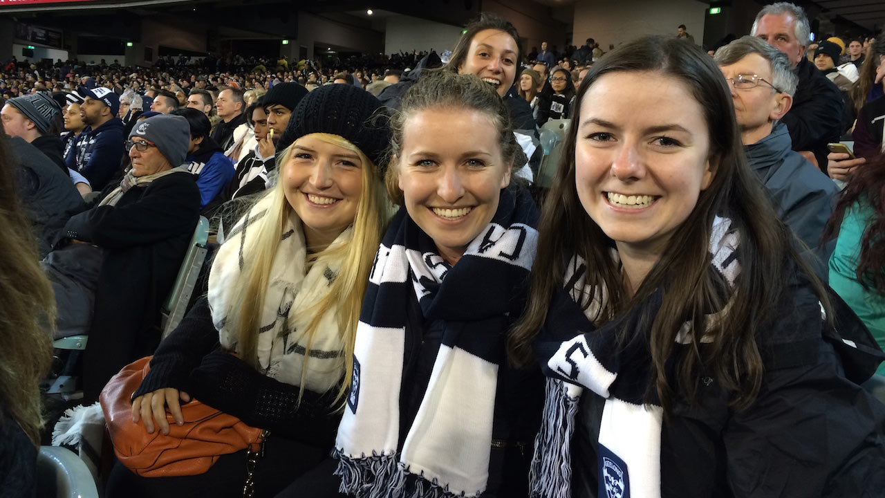 Four women dressed in spirited clothes sit smiling in a crowded stadium