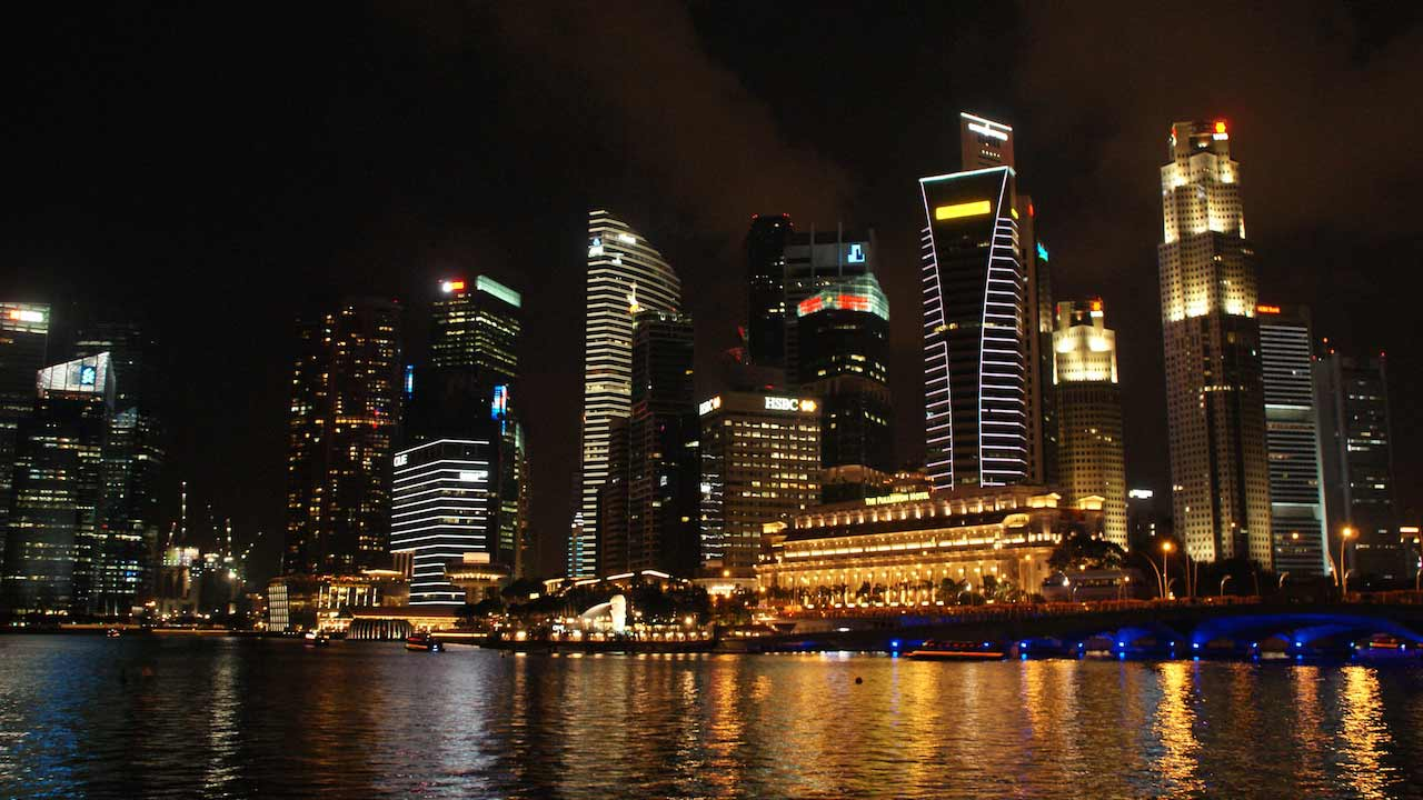 Nighttime illuminated skyline along the harbor in Singapore