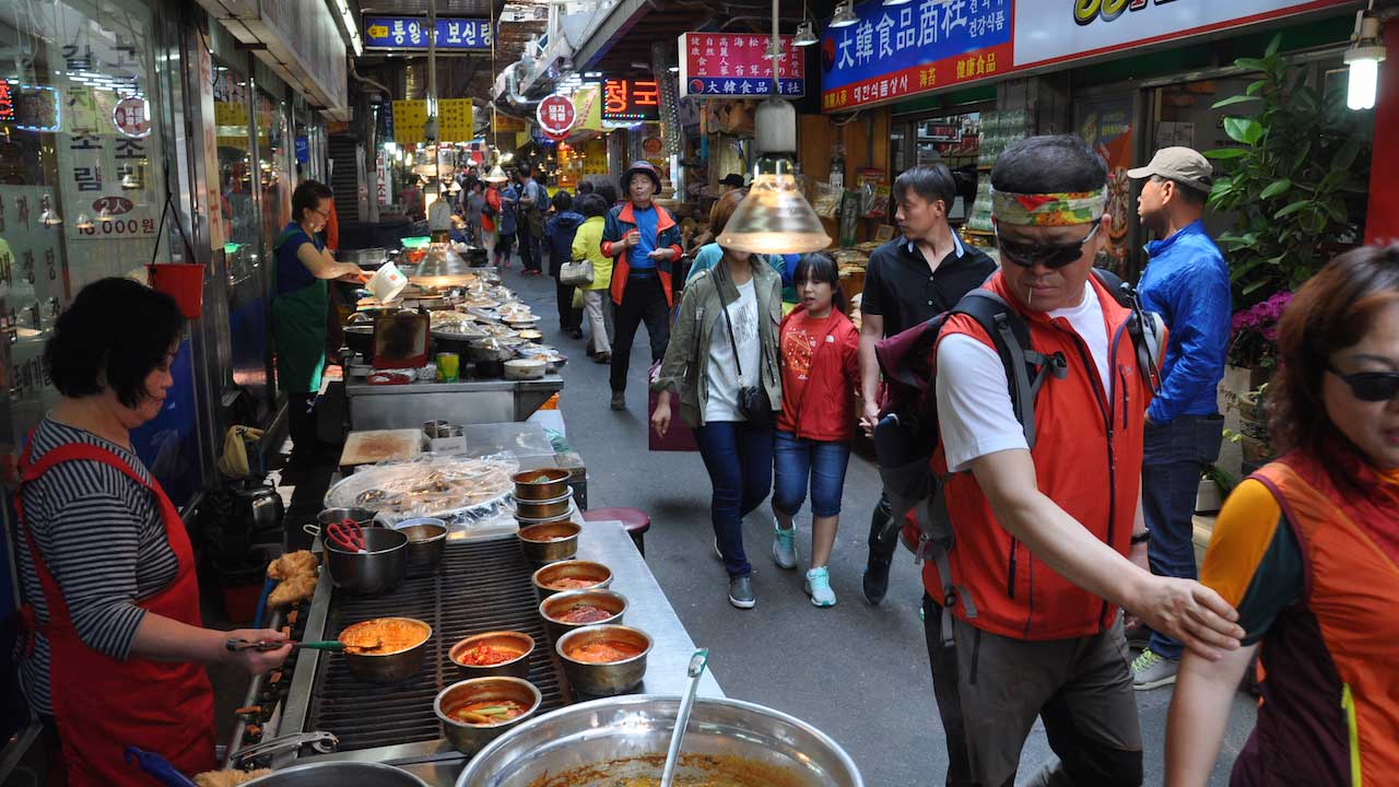 A busy laneway of shops and street food in Seoul