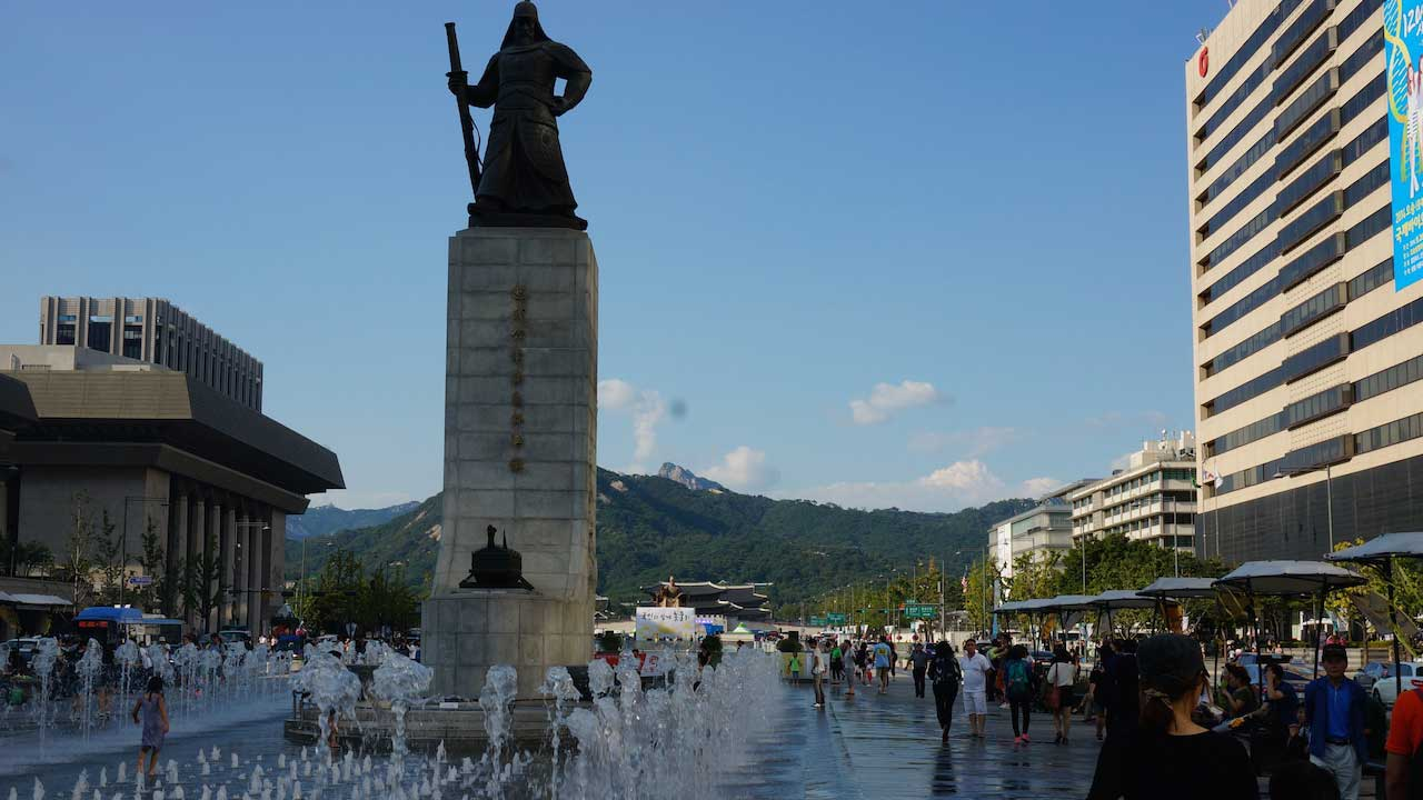 People walk around fountain and a statute surrounded by buildings in Seoul