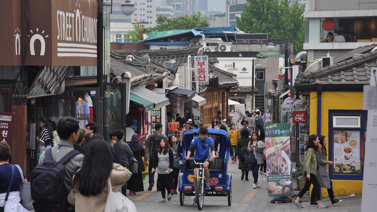A man rides a bicycle attached to a transport for passengers up a busy street in Seoul