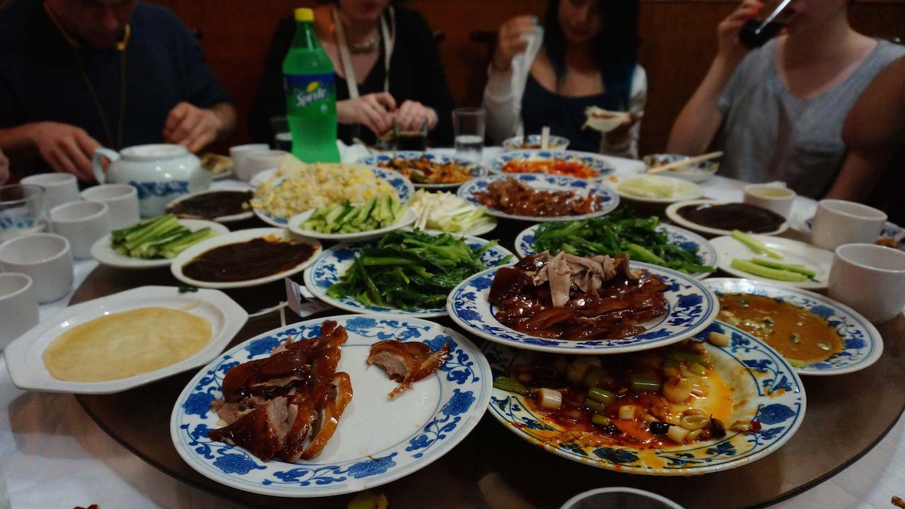 Plates of Chinese food stacked high at a table surrounded by students in Shanghai