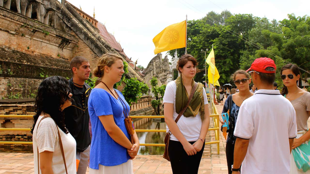 A group of students listen to a guide while standing at Wat Chedi Luang in Chiang Mai, Thailand
