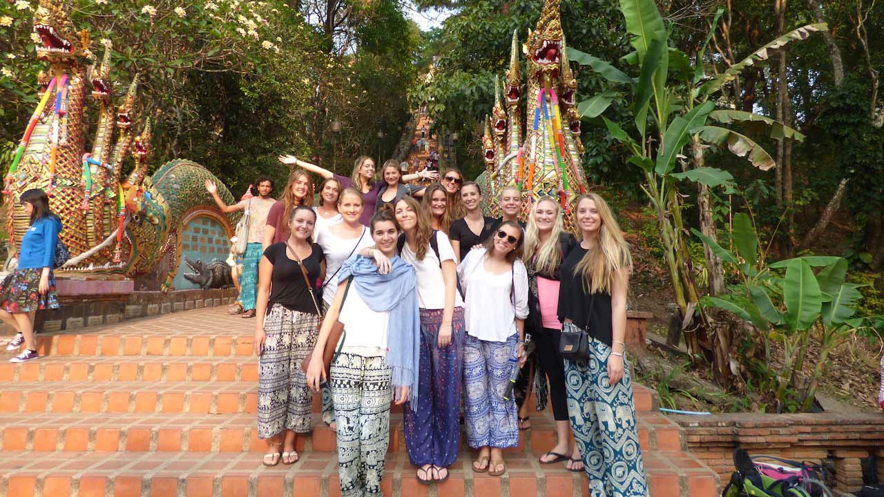 A group of women stand posing at the base of Wat Doi Suthep in Chiang Mai, Thailand