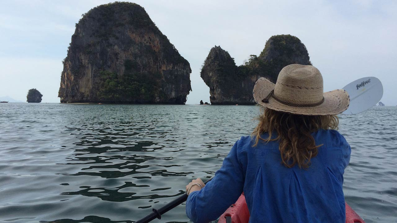 The back of a girl paddling a kayak in the ocean towards limestone cliffs in Railay, Thailand