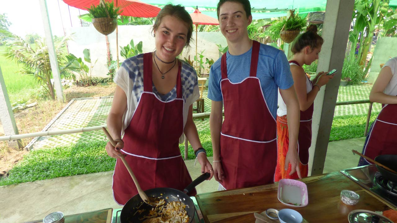 Two students wearing aprons pose with a wok of pad thai that they are cooking at a cooking class in Chiang Mai, Thailand