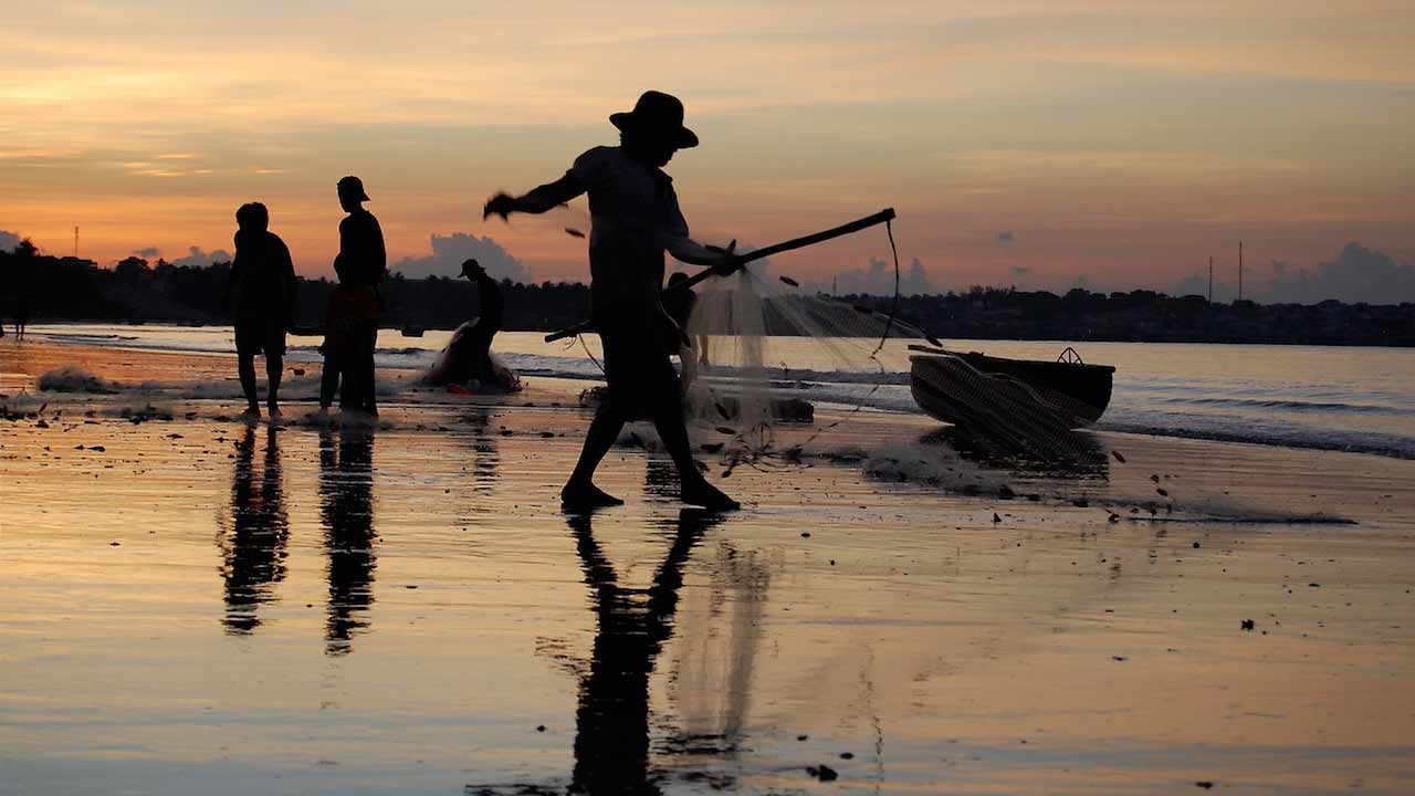 Silhouette of a fisherman and his net at dawn on the shore in Vietnam