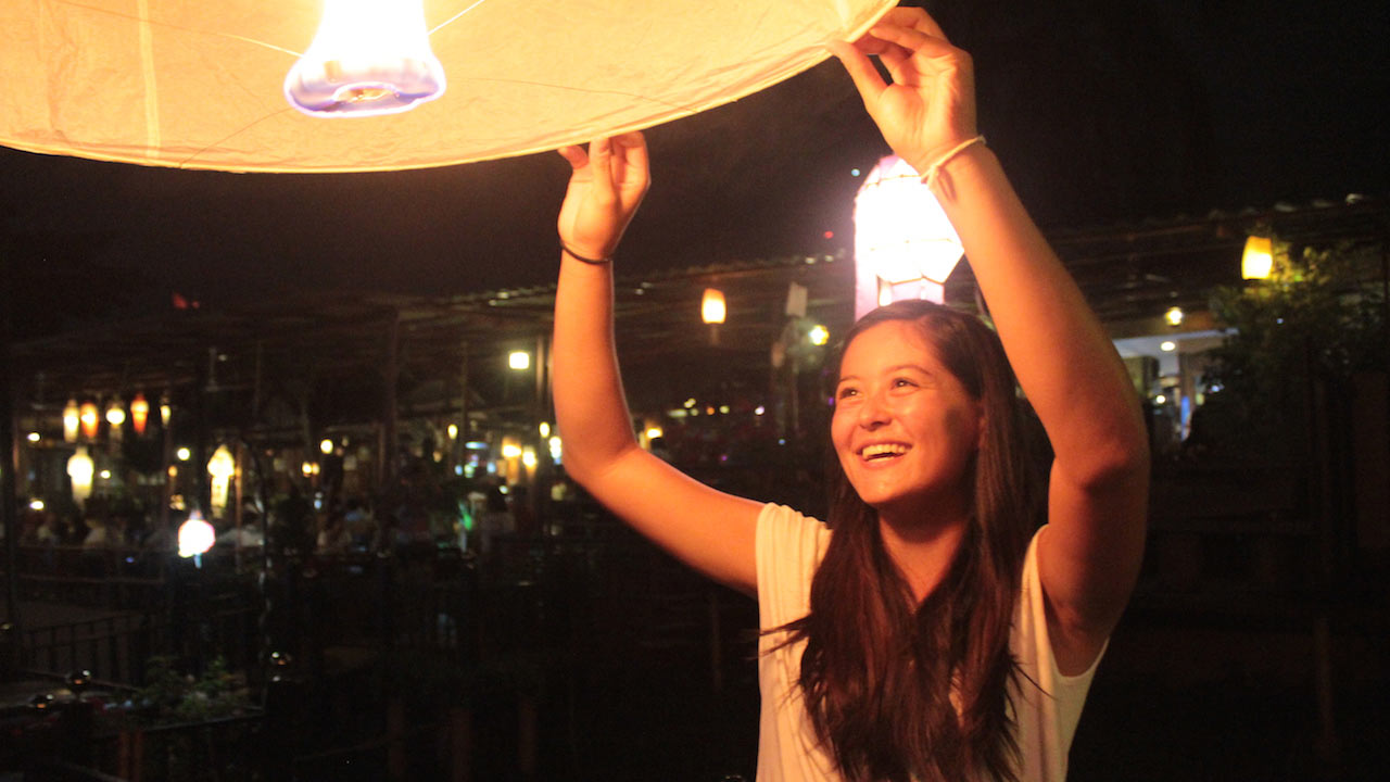 A female student letting go of a lit lantern at nighttime in Thailand