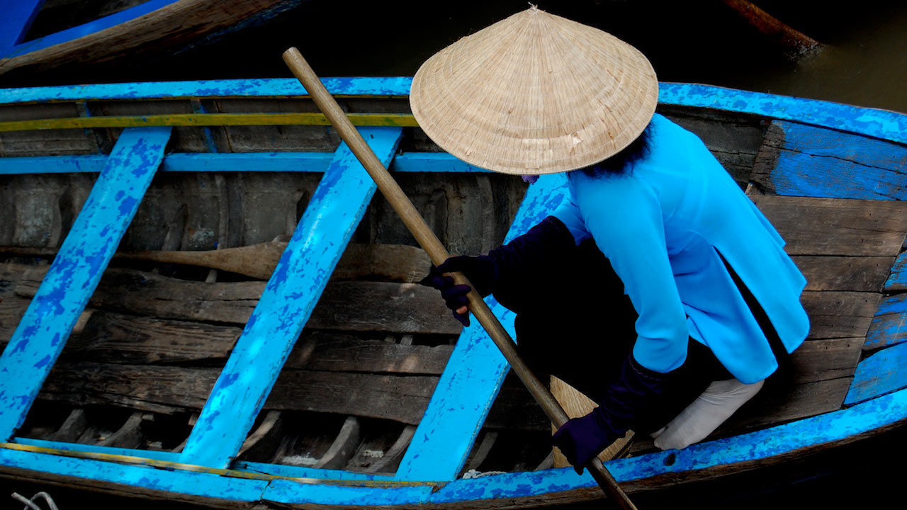 A person wearing a blue shirt and traditional Vietnamese hat rowing a painted blue boat in Vietnam