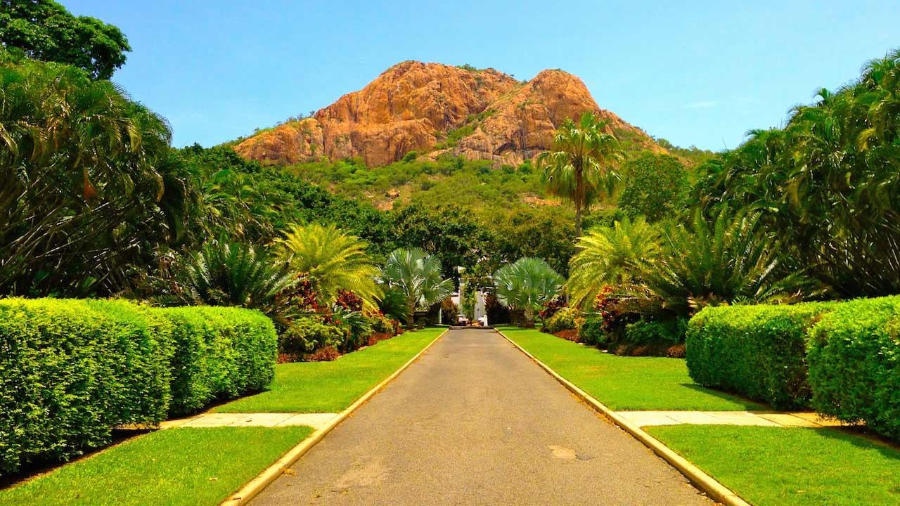 A pathway cuts through a lush, manicured garden in Townsville, Australia